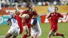 Canada's Brittany Waters, center, takes possession of the ball, during the semi final match of the Women's Rugby World Cup 2014 between France and Canada, at the Jean Bouin stadium, in Paris, Wednesday, Aug. 13, 2014. Canadian coach Francois Ratier has made two changes to his starting lineup for Saturday's women's rugby test match with England. Brittany Waters comes in for Elissa Alarie on the wing and Tyson Beukeboom takes over at lock for Kayla Mack. (Remy de la Mauviniere/THE ASSOCIATED PRESS)