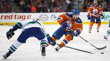 Taylor Hall of the Edmonton Oilers tries to skate past Dan Hamhuis of the Vancouver Canucks on March 18, 2016 at Rexall Place in Edmonton. (Codie McLachlan/Getty Images)