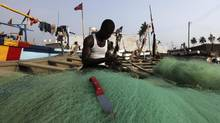 A fisherman prepares his net near Elmina castle, Ghana, Dec. 21, 2012. Although about 52 per cent of Ghanaians live on less than $2 a day, the middle class is growing rapidly. (Luc Gnago/Reuters)