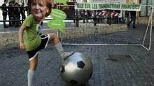 "A demonstrator wearing a mask depicting German Chancellor Angela Merkel poses as she simulates playing a soccer match to protest against the euro zone debt crisis, in front of the Chigi palace in Rome, June 22, 2012. The message on the goal post reads: ""Tax on the financial transactions"". (Remo Casilli/REUTERS)"