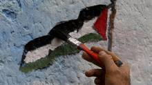 An artist paints a Palestinian flag, part of a larger mural in Jebaliya, northern Gaza Strip. (HATEM MOUSSA/Hatem Moussa/AP)
