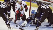 Ottawa Senators' Jason Spezza, centre, tries to knock in the loose puck in front of Tampa Bay Lighting's goalie Antero Niittymaki at the Brandt Centre in Regina, Sask., Monday, Sept. 21, 2009. (TROY FLEECE)