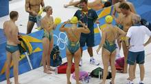 The Australian swim team listens to a coach at the main pool of the Aquatics Centre earlier this week. Not everyone is a fan of the cross-pollination of national coaches for Olympic swimmers. (DAVID GRAY/REUTERS)