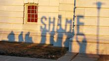 """Shadows of protesters holding letters spelling the word """"SHAME"""" are seen on Wisconsin's state capitol after Republicans pushed through a controversial bill that will strip public workers unions of most of their bargaining rights on Thursday, March 10, 2011 in Madison, Wisconsin. (MIRA OBERMAN/AFP/Getty Images)"""