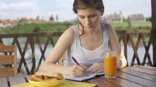 Woman eating and sitting on terrace writing (Jupiterimages/Getty Images/Creatas RF)