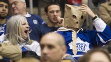 A women yawns, left, as a Toronto Maple Leafs fan wears a paper bag on his head as the Maple Leafs play against the Tampa Bay Lightning during second period NHL hockey action in Toronto on Thursday, April 5, 2012. (Nathan Denette/THE CANADIAN PRESS)