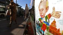 People walk past a cartoon depicting Russian President Vladimir Putin in St. Petersburg. Russian workers painted a depressing picture of corruption and crony capitalism. (Dmitry Lovetsky/Associated Press)