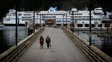 Two women walk along a boardwalk as the BC Ferries vessel Queen of Oak Bay is docked at the Horseshoe Bay ferry terminal in West Vancouver, B.C., in March 2013. (Darryl Dyck for The Globe and Mail)