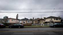 The proposal would see single-family homes such as these on Slocan Street, across from John Norquay Elementary School, rezoned for row and townhouses. (DARRYL DYCK FOR THE GLOBE AND MAIL)