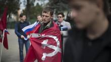A pro-Russian protester wears a soviet flag in front of Crimea's regional parliament building in Simferopol, Ukraine, March 14, 2014. (URIEL SINAI/NYT)