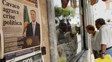 "People look at the front pages of newspapers displayed behind the window of a shop in Ericeira village, 40 km (24 miles) north of Lisbon July 11, 2013. Portugal's political crisis deepened on Thursday after the president rejected a plan to heal a government rift and critics accused him of igniting a ""time bomb"" by calling for early elections next year. President Anibal Cavaco Silva proposed a cross-party agreement between the ruling coalition and opposition Socialists to guarantee wide support for the austerity measures needed for Portugal to exit its bailout next year, followed by elections. The headlines of the newspaper on the wall reads, ""Cavaco deepens political crisis"". (Jose Manuel Ribeiro/Reuters)"