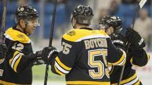 Boston Bruins forward Jarome Iginla, left, and forward Ryan Spooner congratulate defenceman Johnny Boychuk on his goal again the Winnipeg Jets during first period NHL pre-season hockey action in Saskatoon on Friday, Sept 27, 2013. (LIAM RICHARDS/THE CANADIAN PRESS)