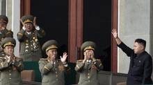 In this April 14, 2012, file photo, North Korean leader Kim Jong-un, right, waves as North Korean military officers clap at a stadium in Pyongyang. (Ng Han Guan/Associated Press)