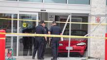 Police investigate after a car backed through the entrance of Costco in London, Ont., on Friday, July 25, 2014. Six people were injured, including a child who was in critical condition, after a car crashed through the front doors of a busy Costco store. THE CANADIAN PRESS/ Geoff Robins