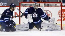 Winnipeg Jets goaltender Ondrej Pavelec reaches for a shot with teammate Eric Tangradi in the crease during second period NHL hockey action in Winnipeg, Tuesday, January 7, 2014. (Trevor Hagan/THE CANADIAN PRESS)