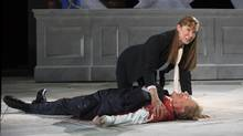 """Elizabeth Marvel as Antony and Gregg Henry as Caesar in the play """"Julius Caesar"""" at the Delacorte Theater in New York, May 21, 2017. The Public Theater's production has been engulfed in controversy, ever since a bootleg video of the assassination of Caesar, styled and performed to suggest Donald Trump, began circulating on the internet. (SARA KRULWICH/NYT)"""