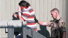 Randall Hopley covers his face as he is taken into his sentencing hearing at the courthouse in Cranbrook, B.C., on July 18, 2012. (Bill Graveland/The Canadian Press)