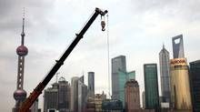 A crane hoists construction material in front of a backdrop of high rising buildings in Shanghai (Eugene Hoshiko)