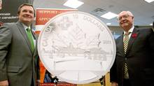 Finance Minister Jim Flaherty, left, joins Royal Canadian Mint chairman Jim Love to unveil a Highway of Heroes commemorative coin at Quinte West City Hall on Oct. 31, 2011. (LARS HAGBERG/THE CANADIAN PRESS)
