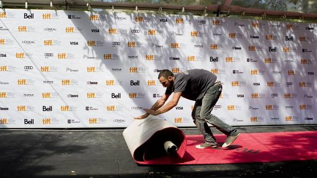 A worker rolls out the red carpet at Roy Thompson Hall as final preparations are made for the Toronto International Film Festival in Toronto on Wednesday, September 5, 2012. (Chris Young/THE CANADIAN PRESS)