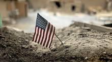 An American flag is placed in a dirt-filled barrier outside the headquarters of 3rd Platoon, 1-320 Field Artillery Regiment, 101st Airborne Divivion, at Combat Outpost Nolen in the Arghandab Valley north of Kandahar. (BOB STRONG/BOB STRONG/REUTERS)