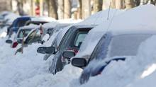 Cars are shown buried in snow in Montreal, Friday, Dec. 28, 2012, following the first major snowstorm of winter in that region. (Graham Hughes/THE CANADIAN PRESS)