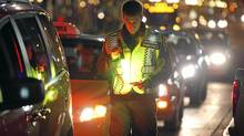 A Victoria Police Reserve Constable looks at a driver's license during a check stop on Yates St. in downtown Victoria. (Chad Hipolito For The Globe And Mail/Chad Hipolito For The Globe And Mail)