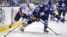 New York Islanders forward P.A. Parenteau tries to get past Toronto Maple Leafs defenceman Carl Gunnarsson in Toronto, March 20, 2012. (Mike Cassese/Reuters/Mike Cassese/Reuters)
