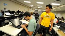 Michael Gorion, right, monitors students as they take exams at the University of Central Florida College of Business Testing Lab in Orlando in 2010. (Steve Johnson/The New York Times)