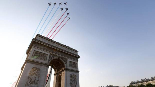 Alphajet planes from the Patrouille de France (France's Patrol) fly over the Arc de Triomphe as the pack of riders cycles on the Champs Elysees Avenue during the 133.5km final stage of the centenary Tour de France cycling race from Versailles to Paris Champs Elysees, July 21, 2013. (JEAN-PAUL PELISSIER/REUTERS)