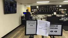 A customer stands at the counter of a cannabis store in Salem, Ore.. The shop's future is in jeopardy after a vote in favour of prohibiting pot firms in unincorporated parts of the county. (Andrew Selsky/AP)