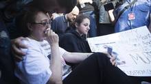 Mother Sahar Bahadi is comforted as she sits next to sister Sarah Yatim at a vigil on Monday, July 29, 2013 at the spot where son and brother Sammy Yatim was shot nine times and killed by Police early Saturday morning in Toronto. (Michelle Siu/THE CANADIAN PRESS)