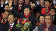 South Korea's presidential candidate Park Geun-Hye waves as she holds a bouquet of flowers after arriving at the headquarters of the ruling Saenuri party in Seoul December 19, 2012. (Kim Jae-Hwan/REUTERS)