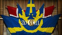 The Swedish and the Norwegian flags with a representation of Swedish industrialist Alfred Nobel are displayed at the Stockholm Concert Hall on December 10, 2011 in Stockholm. (JONATHAN NACKSTRAND/JONATHAN NACKSTRAND/AFP/GETTY IMAGES)