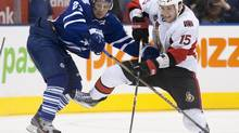 Toronto Maple Leafs' John-Michael Liles, right, battles for the puck with Ottawa Senators' Zack Smith during third period NHL action in Toronto on Saturday October 8, 2011. (Chris Young/THE CANADIAN PRESS)
