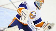 New York Islanders goalie Dwayne Roloson stops the puck during the first period of an NHL hockey game against the Washington Capitals, Wednesday, Oct. 13, 2010, in Washington. (AP Photo/Nick Wass) (Nick Wass)