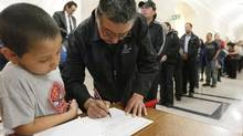 Manitobans line up to pay their respects and sign a book of condolences for Elijah Harper at the Manitoba Legislature on May 20, 2013. (JOHN WOODS/THE CANADIAN PRESS)
