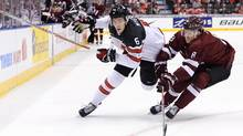 Canada defenceman Philippe Myers battles for the puck with Latvia defenceman Kristaps Zile during their world junior game in Toronto on Thursday night. (Nathan Denette/THE CANADIAN PRESS)