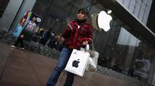 A customer walks out after shopping at an Apple store in downtown Shanghai, Feb. 28, 2012. (CARLOS BARRIA/REUTERS)