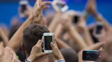 A member of the audience uses an iPhone to record DJ Afrojack's performance on ABC network's Good Morning America program in New York June 27, 2014. (LUCAS JACKSON/REUTERS)