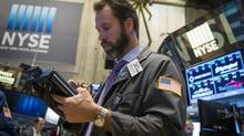 A trader works on the floor of the New York Stock Exchange shortly after the markets open in New York on Nov. 7, 2014. (LUCAS JACKSON/REUTERS)