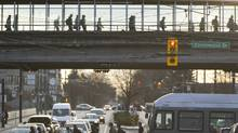 Commuters cross over the road on a pedestrians bridge over Broadway in transit between Skytrains at the Broadway and Commercial Sky Train terminals in Vancouver March 24. (John Lehmann/The Globe and Mail/John Lehmann/The Globe and Mail)