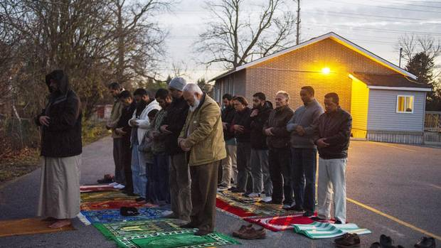 Congregation members hold prayer in the parking lot on Sunday.