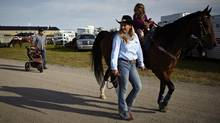 Professional barrel racer Tammy Fischer, left, leads her daughter Sydney on Round Pen after competing in the slack competition at the High River rodeo in High River, Alta., Thursday, June 21, 2012. Fisher won the 2010 Calgary Stampede barrel racing championship then announced to the crowd she had just lost her teenage son in a car accident in Texas. She has continued to ride at rodeos all over North America and has established a scholarship fund in her son's honour. (Jeff McIntosh For The Globe and Mail)