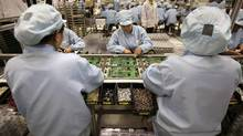 Celestica employees work at a production line in a factory in Dongguan, China's southern Guangdong province. (TYRONE SIU)