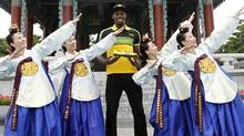 World record holder Usain Bolt (C) of Jamaica poses with his new running spikes and promoters wearing traditional Hanbok in Daegu, southeast of Seoul August 20, 2011. Bolt, the world's fastest man, will compete in the World Athletics Championships in Daegu, held from August 27-September 4. He predicted on Saturday he would retain his world 100 metres title in Daegu easily, provided he gets a decent start. Picture taken August 20, 2011. REUTERS/Lee Jae-Won (Lee Jae-Won/Reuters)