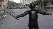 A riot police officer stands in front of anti-government protesters during clashes in Simon Bolivar Square, which leads to Tahrir Square in Cairo, on Jan. 30, 2013. (MOHAMED ABD EL GHANY/REUTERS)