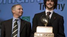 Calgary University Dinos quarterback Erik Glavic holds the Hec Crighton trophy as CIS player of the year for the second time in three seasons while Steve Crighton, grandson of Hec Crighton, left, looks on at awards ceremony Thursday, Nov.26, 2009 in Quebec City. THE CANADIAN PRESS/Jacques Boissinot (Jacques Boissinot)