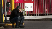 A laid off Aveo employee makes a call in front of the aircraft maintenance company's plant Tuesday, March 20, 2012 in Montreal.THE CANADIAN PRESS/Ryan Remiorz (RYAN REMIORZ/THE CANADIAN PRESS)