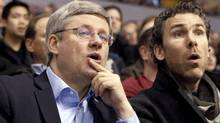 Canadian Prime Minister Stephen Harper and former Vancouver Canuck Trevor Linden react while watching the Vancouver Canucks take on the Minnesota Wild in Vancouver, British Columbia March 14, 2011. REUTERS/Ben Nelms (BEN NELMS)